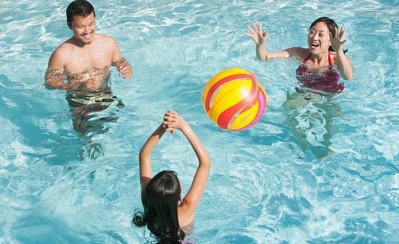 famille jouant au ballon dans la piscine