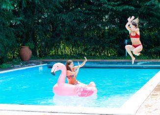 Une maman et sa fille qui s'amusent dans la piscine de leur jardin