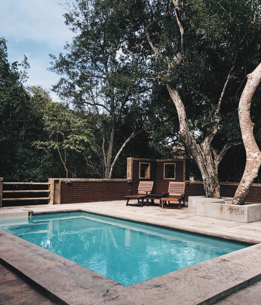 piscine avec margelles effet beton et deux transats en bois sous des arbres
